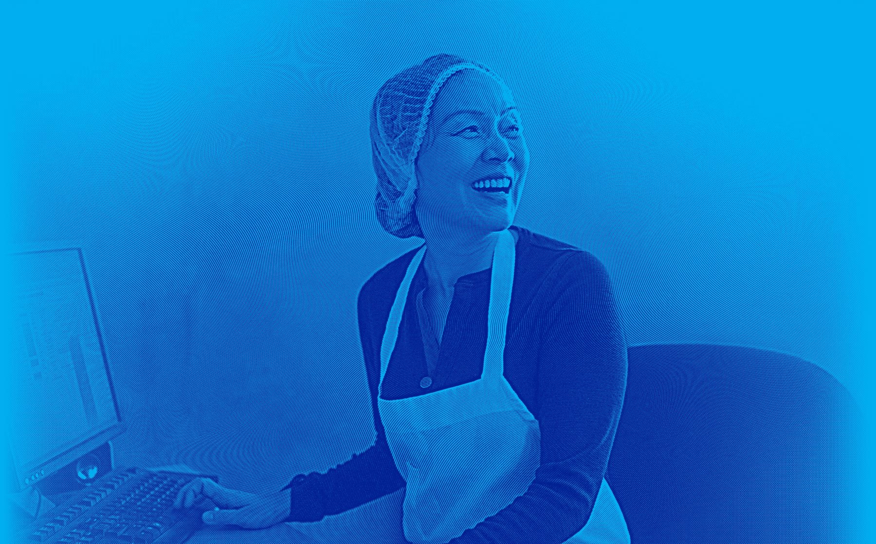 Food processing industry employee smiling as she enters order into a computer