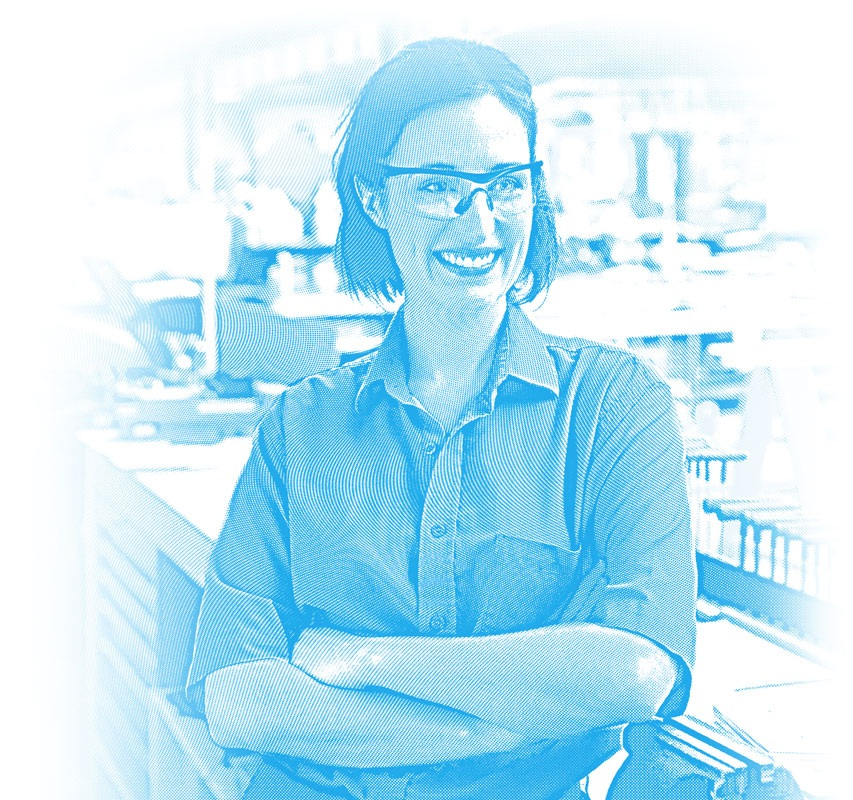 Female production worker wearing safety glasses and smiling at her new job